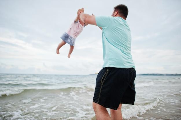 夏休み。親と子供との野外活動。幸せな家族の休日。海砂浜で赤ん坊の娘と父。 Premium写真