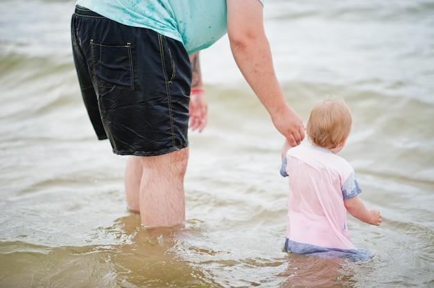 夏休み。親と子供との野外活動。幸せな家族の休日。海の上の赤ん坊の娘を持つ父。