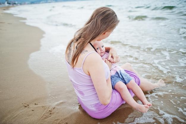 夏休み。親と子供との野外活動。幸せな家族の休日。海砂浜で赤ん坊の娘と妊娠中の母親。