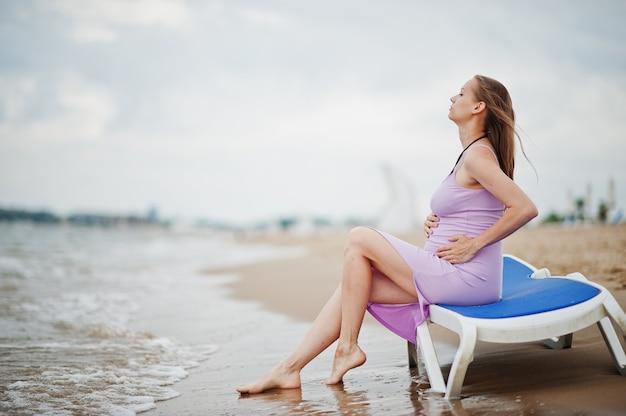 夏休み。海砂浜の妊娠中の母親。
