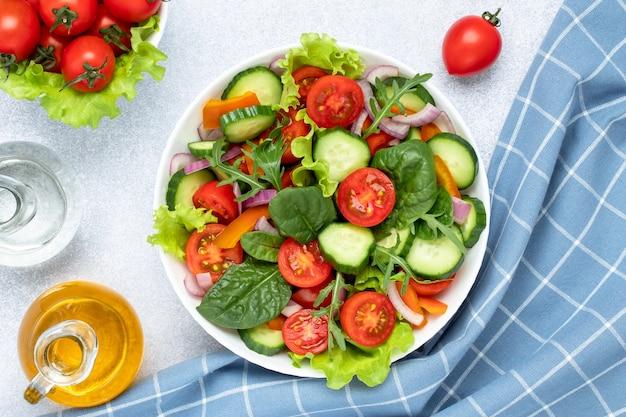 Летний овощной салат с помидорами черри, огурцами, рукколой, базиликом и заправлен оливковым маслом. синяя клетчатая салфетка на сером столе. вид сверху. здоровая диета, крупный план вегетарианской пищи.