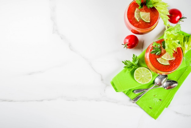 Summer veggie food, cold soup gazpacho in glasses with with fresh celery, parsley and lime juice. white marble background copy space