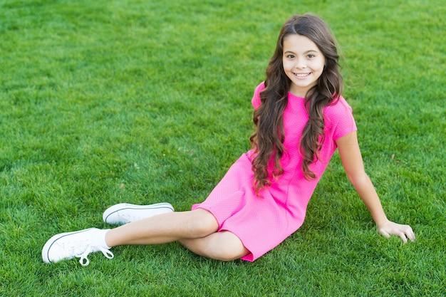 Летние флюиды. маленькая девочка расслабиться на зеленой траве. парки и дачи. весенняя природа. летний пикник. школьница улыбается ребенку в розовом платье. счастливое детство. парк с зеленой травой. отдыхая на зеленой траве.