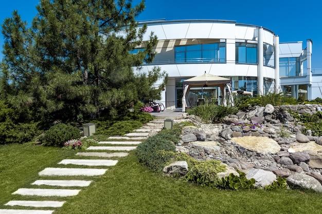 Летний вид на зеленый двор роскошного загородного дома с патио