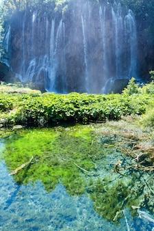 大きな滝と澄んだ湖の夏の景色と緑の植物が底にあります(プリトヴィツェ湖群国立公園、クロアチア)