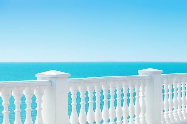 고전적인 흰색 난간과 바다가 내려다 보이는 빈 테라스가있는 여름 전망