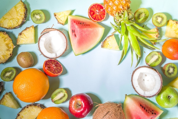 Summer vitamin food concept, various fruit and berries background - watermelon pineapple apples kiwi coconut orange lime creative flat lay on light blue background top view copy space