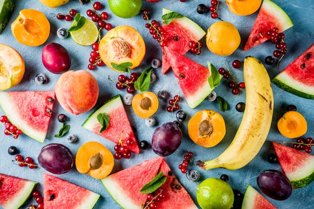Summer vitamin food concept, various fruit and berries watermelon peach mint plum apricots blueberry currant, creative flat lay on light blue background