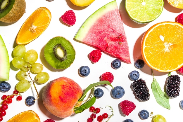 Summer vitamin food concept, various fruit and berries watermelon peach plum apricots blueberry currant, flat lay on white background top view copy