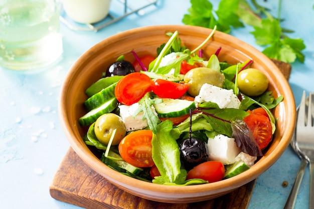 青い石またはコンクリートのテーブルに新鮮な野菜のフェタチーズとブラックオリーブと夏のビタミンサラダギリシャ風サラダのクローズアップ
