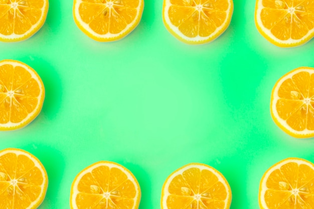 Summer and vitamins background frame. lemon on a green background, minimal food concept
