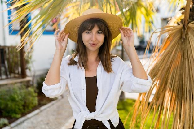 Vportrait di estate della donna graziosa del brunette in cappello di paglia in posa all'aperto.
