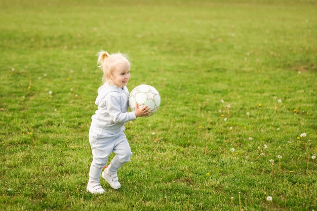 Summer walk, girl on nature. sport family. a little girl play soccer with a ball.