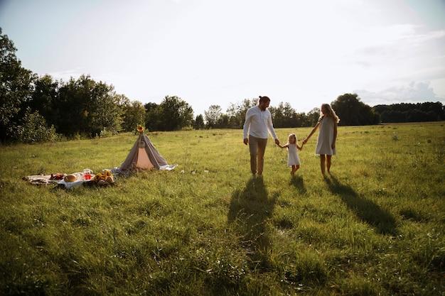 自然の中で幸せな家族の夏の散歩。日没時のシルエット。