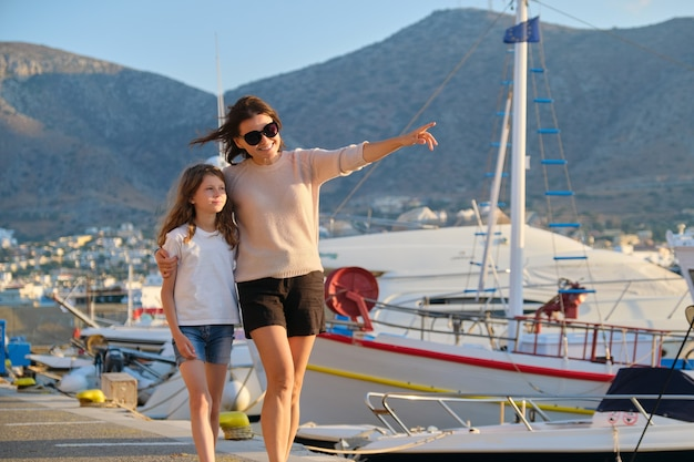 Summer walks on sea pier, mother and daughter child walking together holding hands, background mountain sunset on sea yachts in bay, copy space