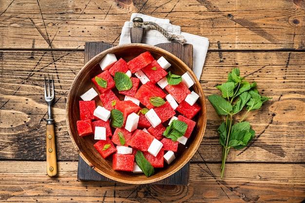 木の板にフェタチーズとミントを添えた夏のスイカのサラダ。木製の背景。上面図。