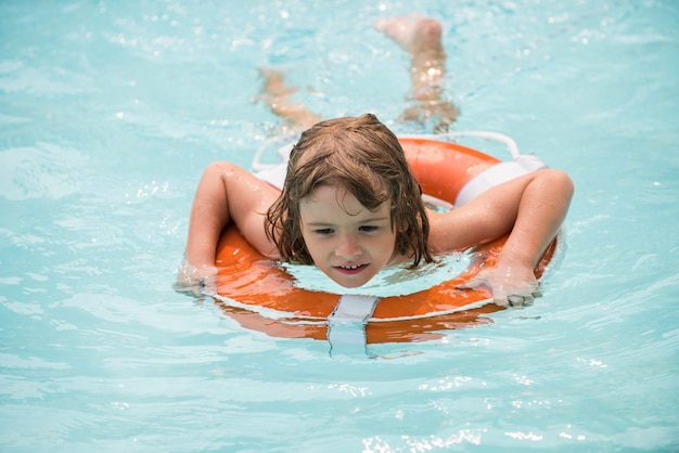 夏の週末のプールリゾートのスミリングボーイ、アクアパークの子供がプールの夏のウォーターアクティビティで泳いでいます...
