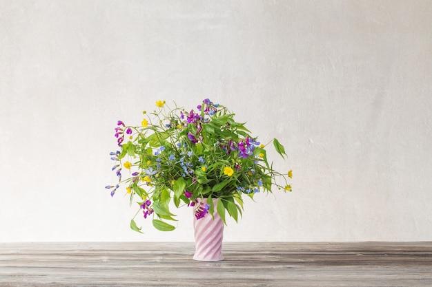 Летние полевые цветы в розовой керамической вазе на белом фоне