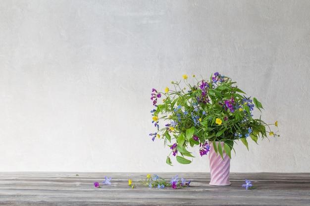 Летние полевые цветы в розовой керамической вазе