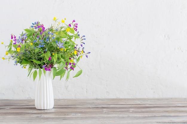 Летние полевые цветы в вазе на белом фоне