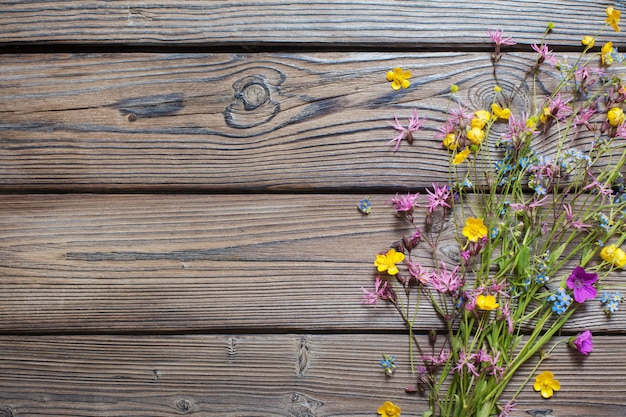Summer wild flowers on wooden surface