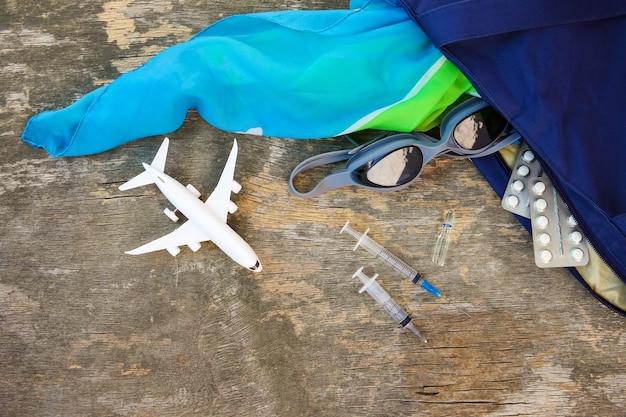 바다 휴가를 위한 여름 여성용 해변 액세서리와 오래된 나무 배경에 알약. 여행에 필요한 약물의 개념. 평면도.