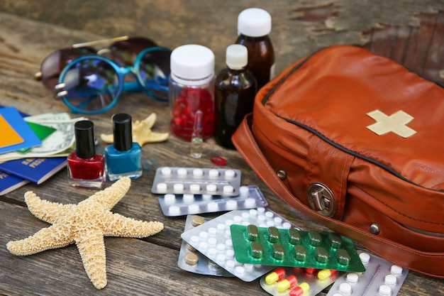 Summer women's beach accessories for your sea holiday and first aid kit on old wooden table. concept of medication required in journey. top view. flat lay.