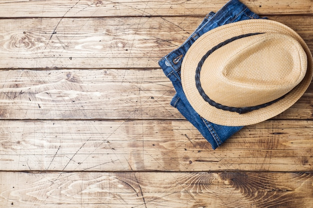 Summer women's clothes. flat lay fashion photo. blue jeans and sun hat on wooden background. copy space