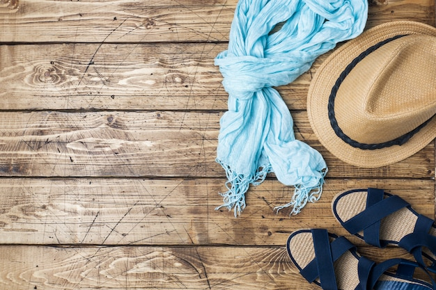 Summer women's clothes. flat lay fashion photo. scarf and sun hat, blue sandals on wooden background. copy space