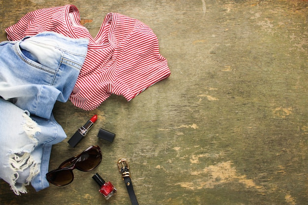 Summer women's clothing and accessories: t-shirt, jeans, lipstick, nail polish, belt, sunglasses. top view.
