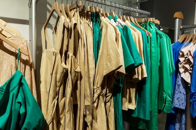 상점의 옷걸이에 유행하는 색상의 여름 여성 의류. 패션과 쇼핑.