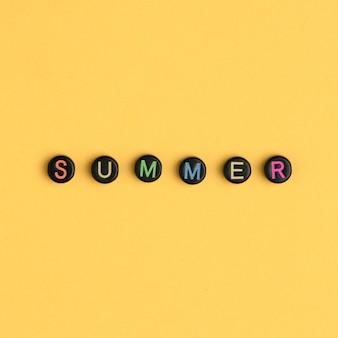 夏の単語ビーズアルファベット黄色の背景