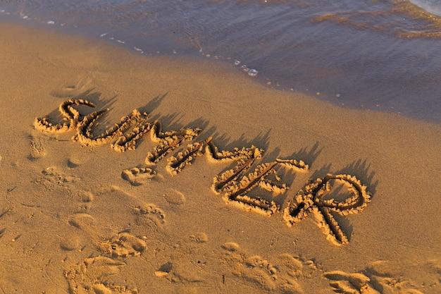 海の近くのビーチの砂に書かれた夏