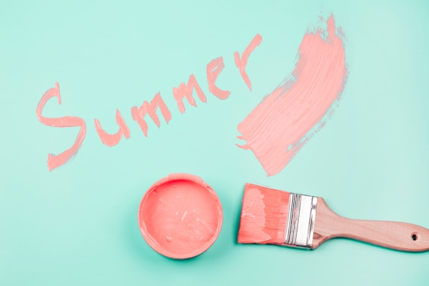Summer written on the mint background with paintbrush and paint container