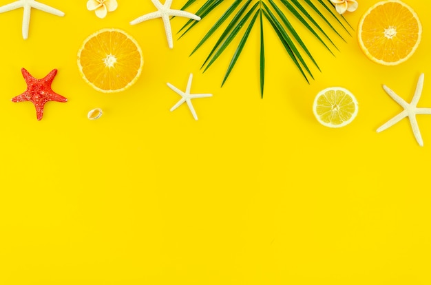 Summer yellow background with palm leaf branch, starfishes and oranges