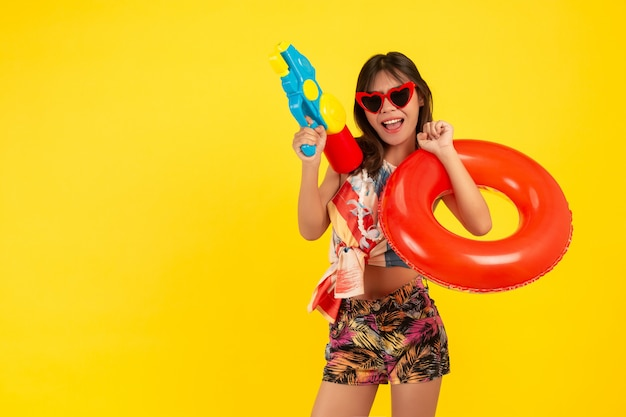 Summer young beautiful woman with water gun and rubber band, songkran holidays