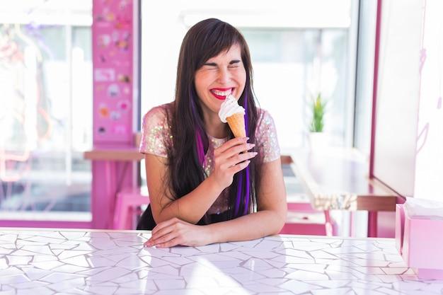 Лето, молодость и концепция десерта - довольно забавная девушка, наслаждаясь мороженым в кафе