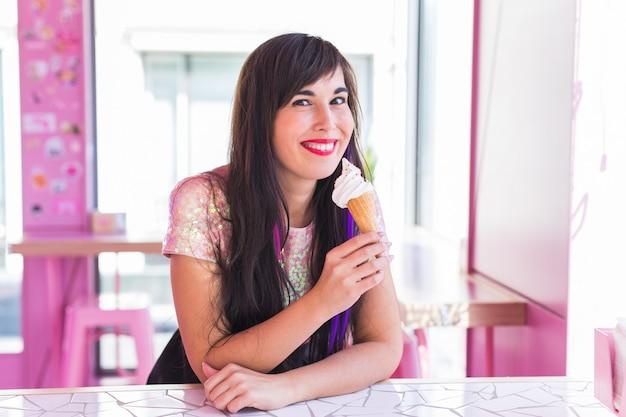 Лето, молодость и десерт концепция - красивая девушка, наслаждаясь мороженое в кафе