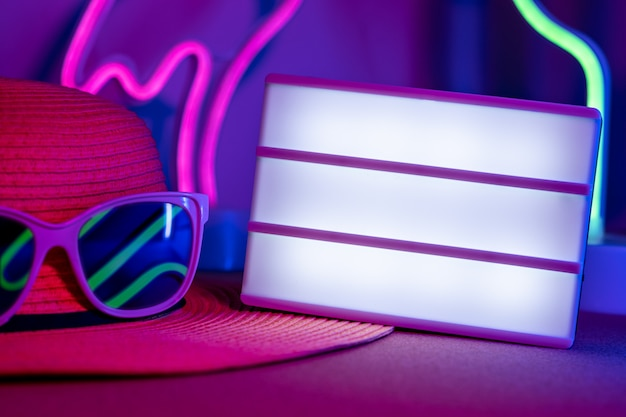 Summerblank light box on hat with sunglasses refection neon pink and blue and green light on table