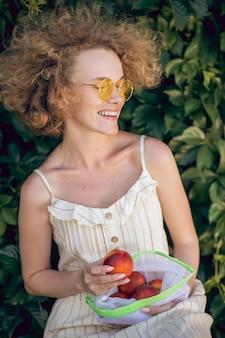 夏時間。ネクタリンを手にした薄手のドレスを着た女性の写真