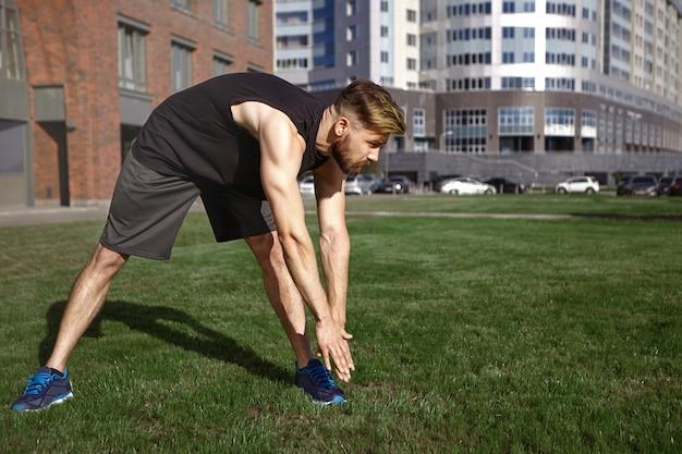 여름철, 활동, 피트니스 및 취미 개념. 근육질의 젊은 유럽 형태가 이루어지지 않은 검은 색 스포츠 옷과 운동화를 왼쪽 발가락으로 구부리고 야외에서 운동하는 동안 다리를 스트레칭