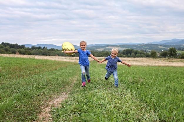 封鎖後の夏。山の牧草地で一緒に走っている子供たち、新しい普通
