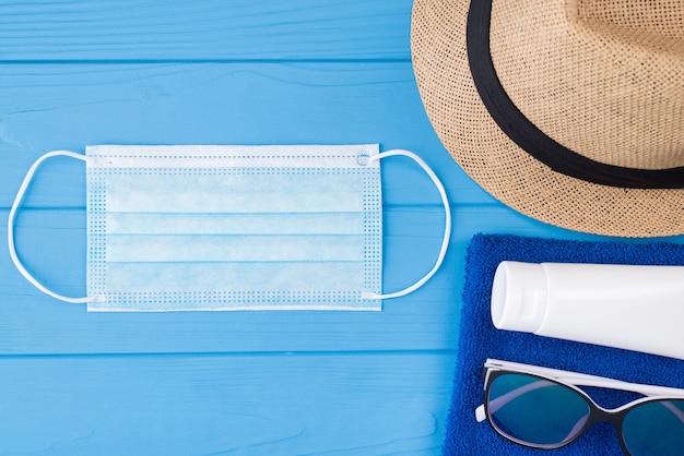 夏と検疫の概念。上の俯瞰図のクローズアップ写真タオルサングラス日焼け止めマスクとコピースペースで青い木製の背景に分離された日よけ帽