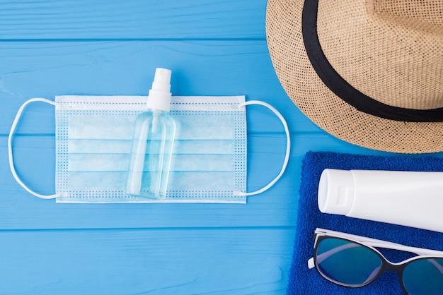 夏と検疫の概念。上の俯瞰図のクローズアップ写真タオルサングラス日焼け止めマスク消毒剤とコピースペースで青い木製の背景に分離された日よけ帽