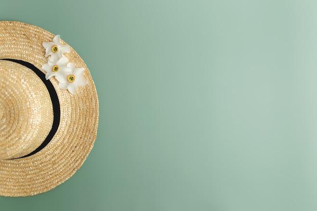 Квартира концепции летней коллекции лежала на зеленом фоне с соломенной шляпой и цветочными головками нарциссов. фото высокого качества