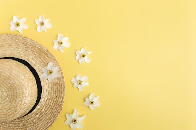 Квартира концепции летней коллекции лежала на желтом фоне с соломенной шляпой и цветочными головками нарциссов. фото высокого качества