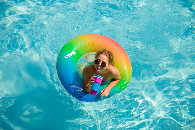 Summertime. enjoying suntan. woman in swimsuit on inflatable circle in the swimming pool.
