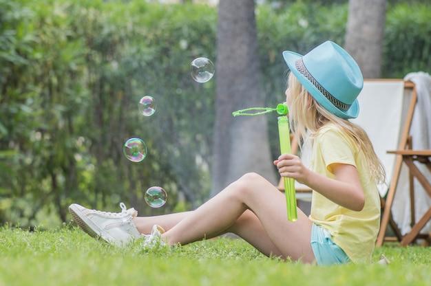 Летнее веселье. милая детская девочка дует мыльные пузыри и развлекается