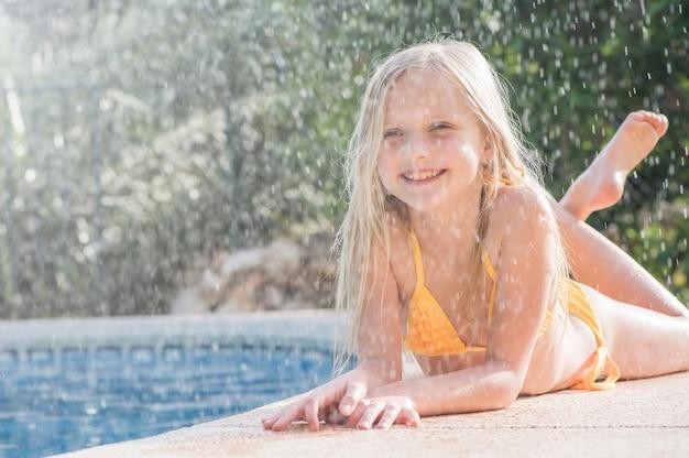 夏の楽しみ。晴れた日にプールで幸せな女の子。