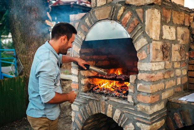 Summertime fun. young man cooking meat on a brick barbecue.